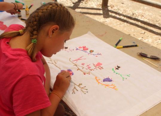 girl at summer camp using fabric marker