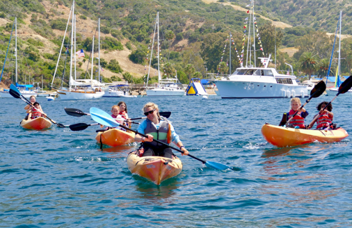 campers on kayaks being lead out of the bay by a counselor