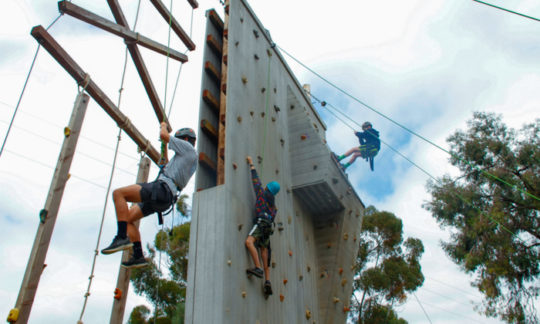 campers climbing and rappelling down from the 30 ft climbing wall