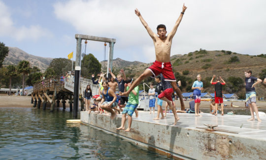 campers jumping off the dock into the water