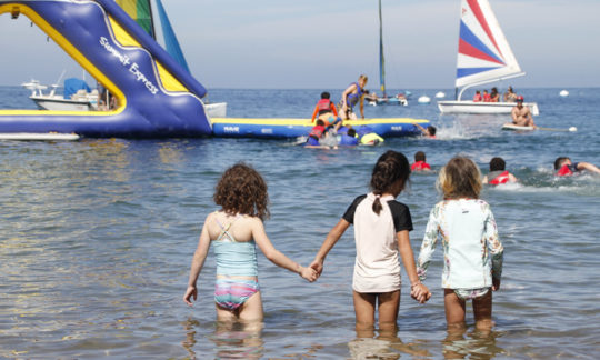 three young girls holding hands in the shallow water
