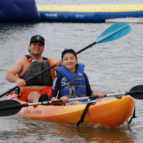 camper and counselor kayaking together through the harbor