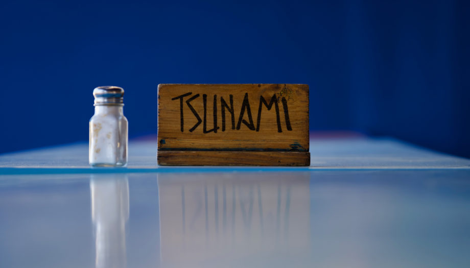 salt shaker on a cafeteria table with a sign for the Tsunami group