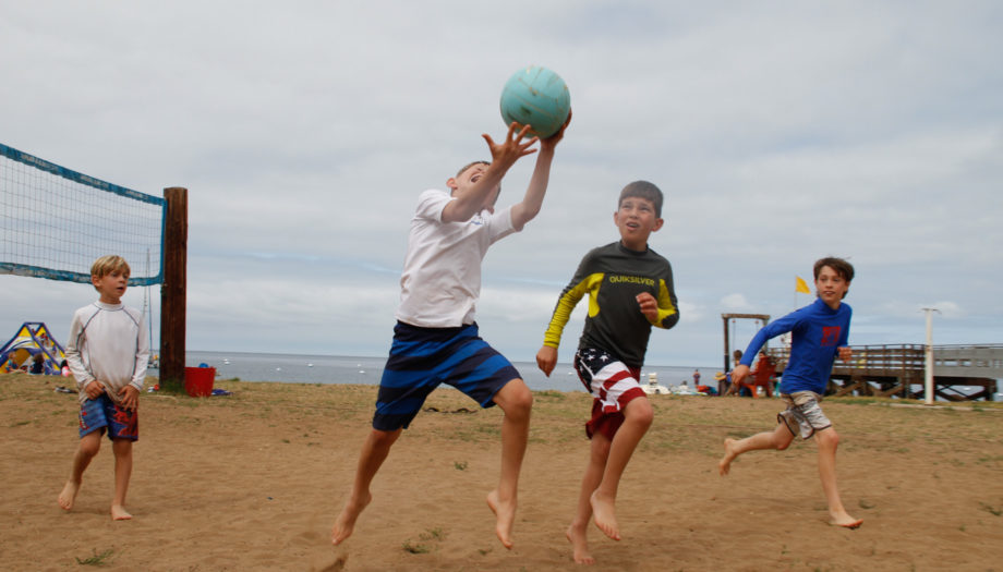 boy catching a ball over his shoulder being chased by another boy