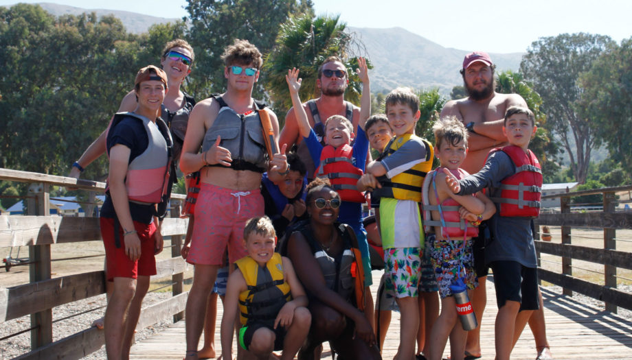staff and campers posing on the dock while wearing life jackets