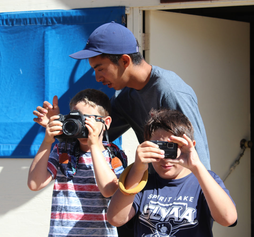 counselor showing campers how to use a DSLR camera