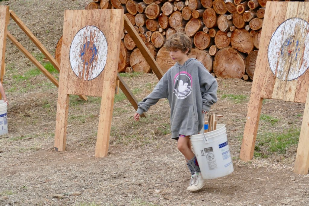 child at camp near archery targets