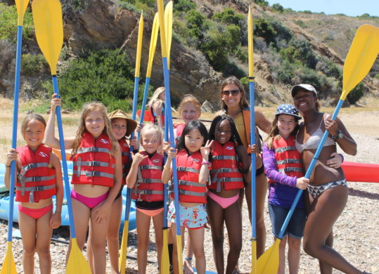 girls at summer camp holding oars