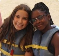 two young women smiling, wearing life jackets and sitting on the beach