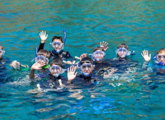 snorkelers in ocean waving at camera