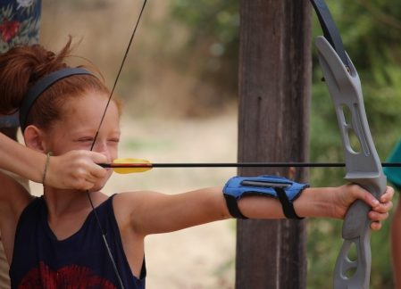 young girl performing archery