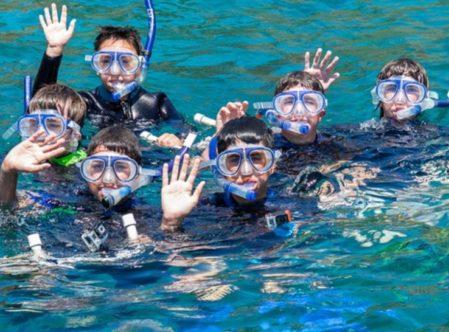 boys waving in water in snorkel gear