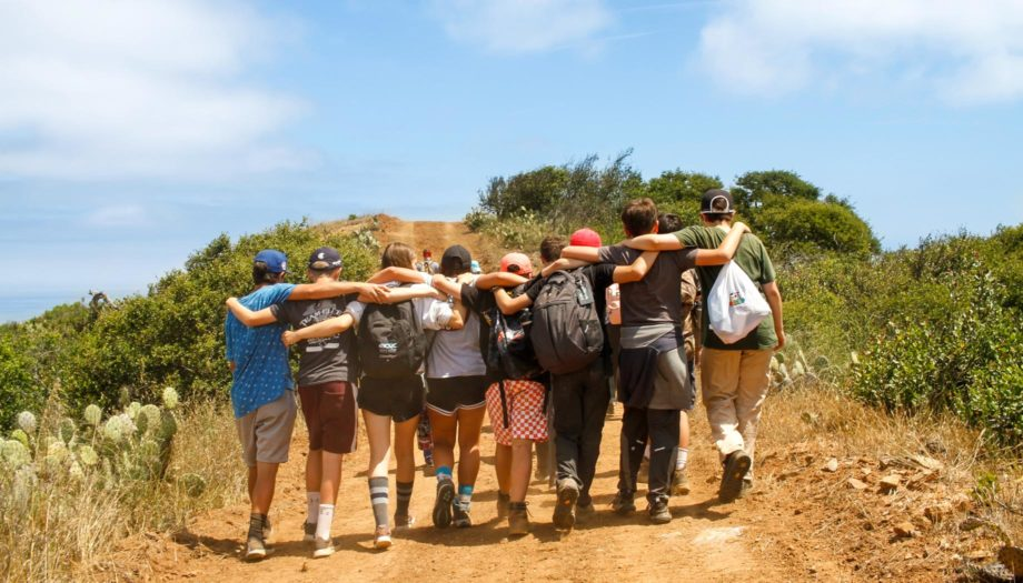 group walking up a hiking trail with arms around each other