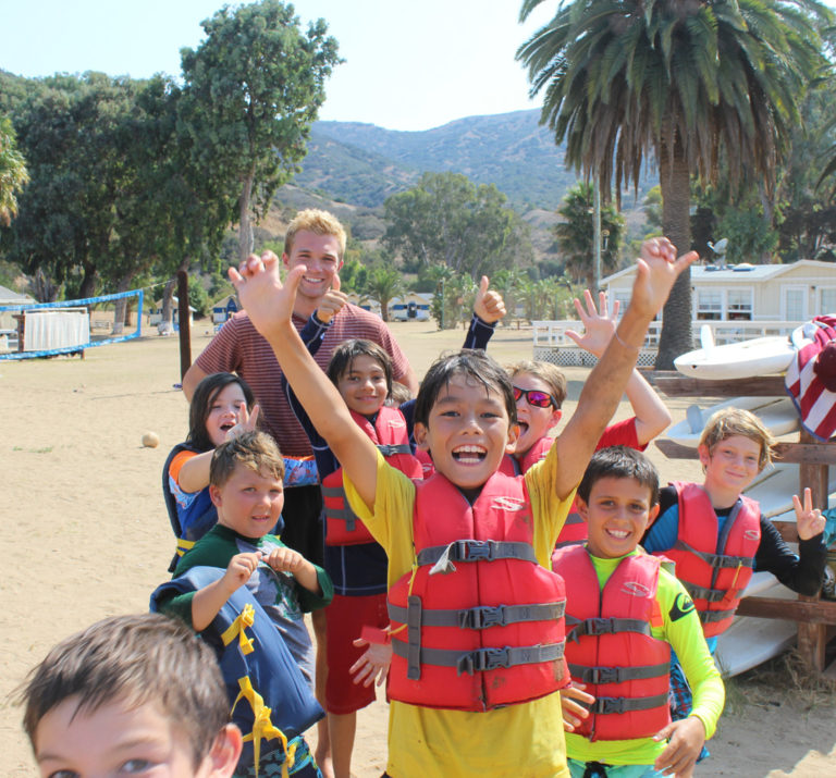 campers smiling with lifejackets on after sailing