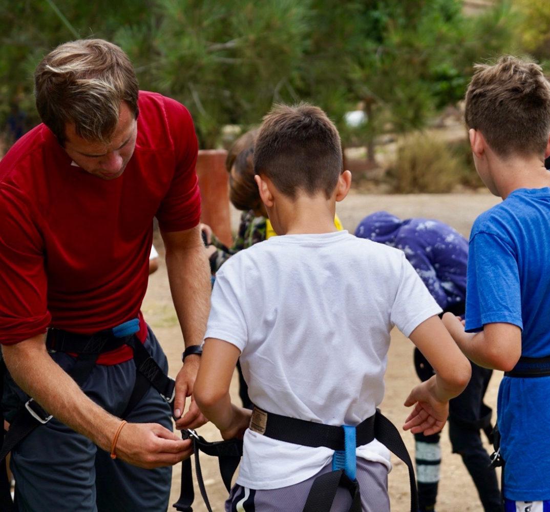 instructor adjusting a camper's safety equipment