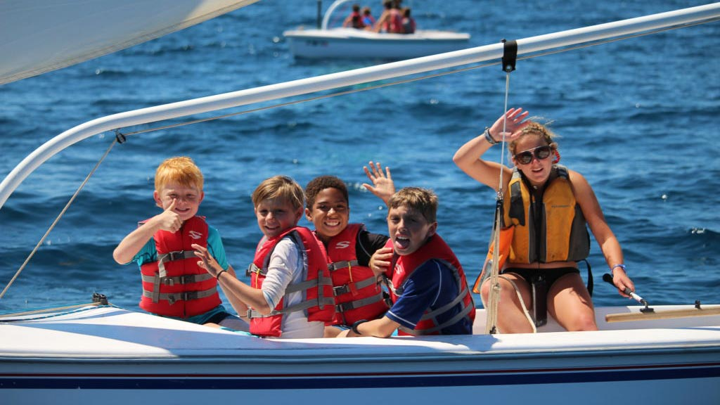 summer campers smiling and waving while on boat in catalina