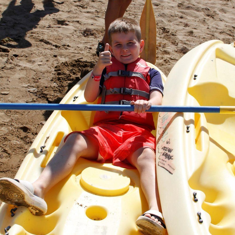 kid wearing lifejacket in kayak